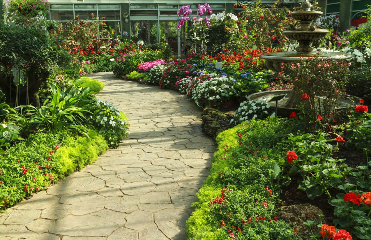 Stamped concrete path in a garden full of plants and flowers